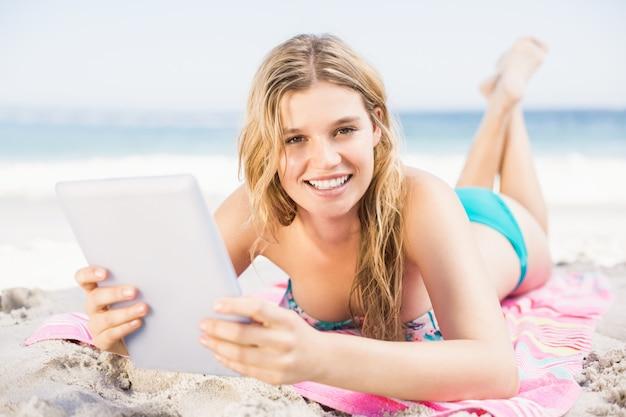 Młoda kobieta używa cyfrową pastylkę na plaży
