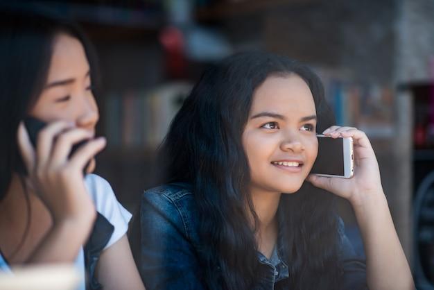 Młoda kobieta używa i patrzejący smartphone z czuć szczęśliwy