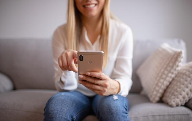 Młoda kobieta używa jej mądrze telefon