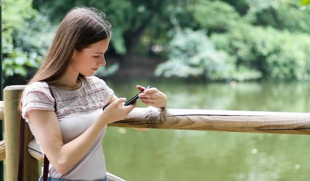 Młoda kobieta używa jej smartphone w parku