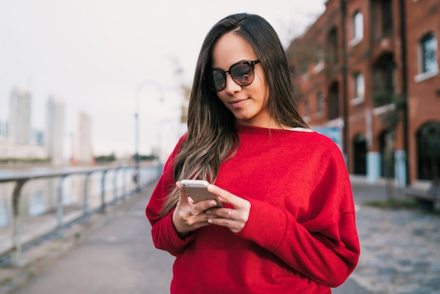 Młoda kobieta używa jej telefon komórkowego.