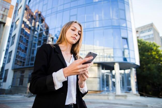 Młoda kobieta używa jej telefonu niskiego kąta strzał