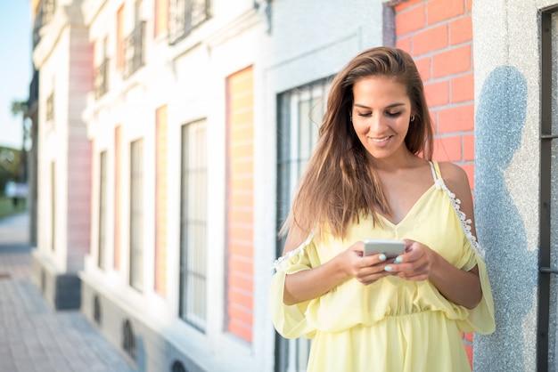 Młoda kobieta używa jej telefonu odizolowywającego zakończenie w górę plenerowego