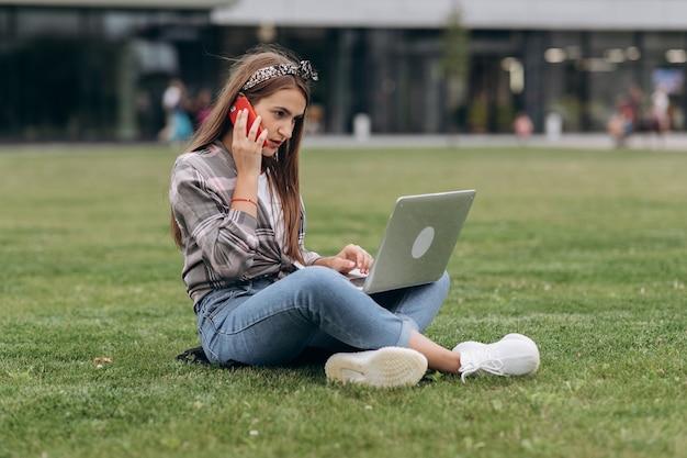 Młoda kobieta używa komputer na zielonych trawach w parku. freelancer pracujący na świeżym powietrzu lub relaksacyjny