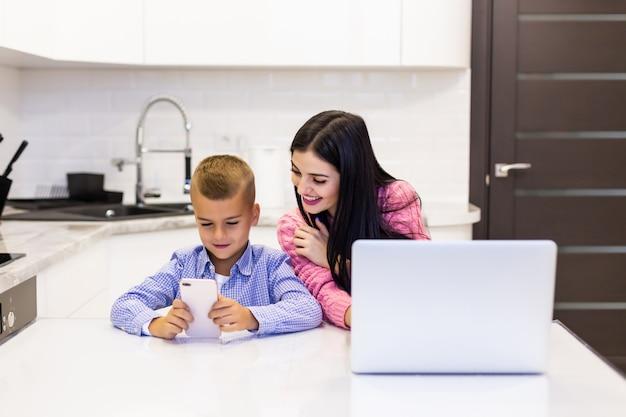 Młoda kobieta używa laptop dla pracy w domu podczas gdy jej syn bawić się gry w telefonie. zajęty młoda kobieta pracuje na laptopie.