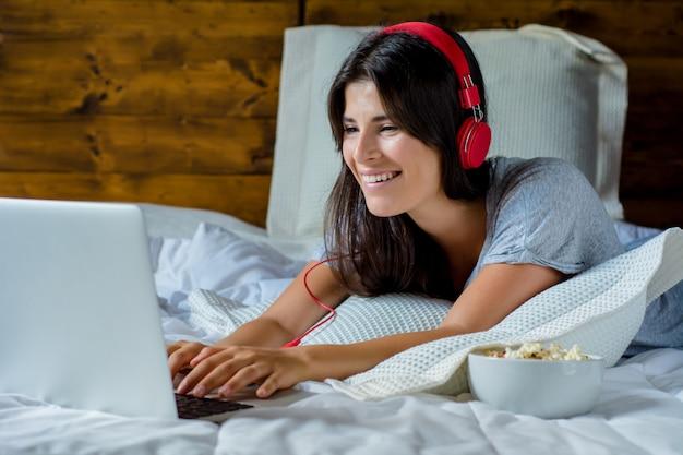Młoda kobieta używa laptop i hełmofony w łóżku.