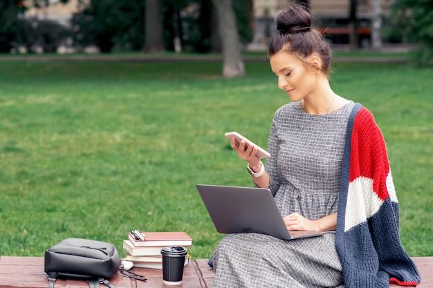 Młoda kobieta używa laptop i telefon na ławce w parku