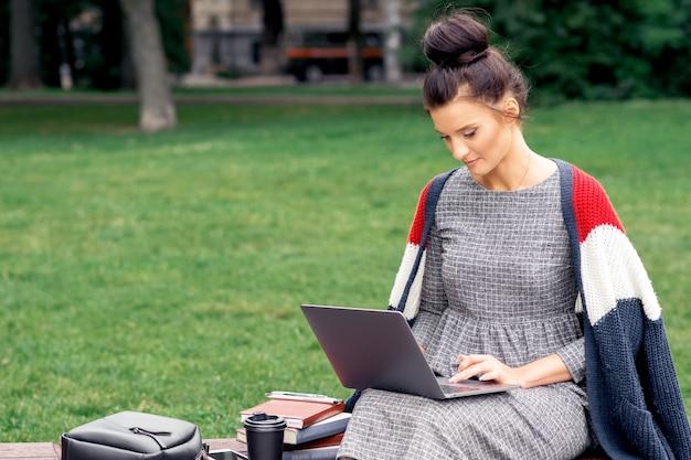 Młoda kobieta używa laptop na ławce w parku