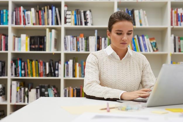 Młoda kobieta używa laptop w bibliotece