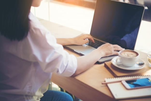 Młoda kobieta używa laptop