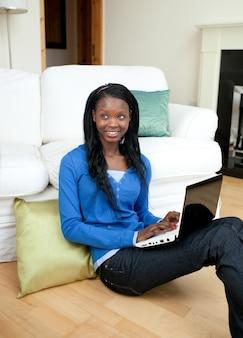Młoda kobieta używa laptopu obsiadanie na podłoga