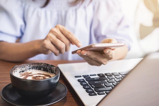 Młoda kobieta używa mądrze telefon i laptop z filiżanką kawy w kawiarni