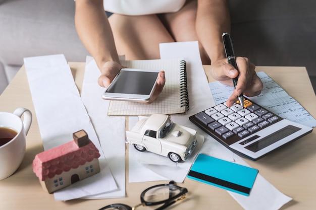 Młoda kobieta używa mądrze telefon i sprawdza rachunki