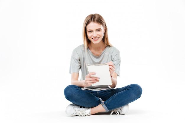 Młoda kobieta używa ołówek i notatnika