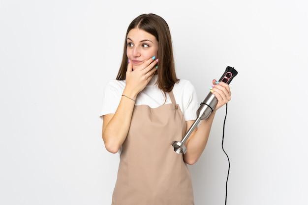 Młoda kobieta używa ręki blender na biel ścianie myśleć pomysł