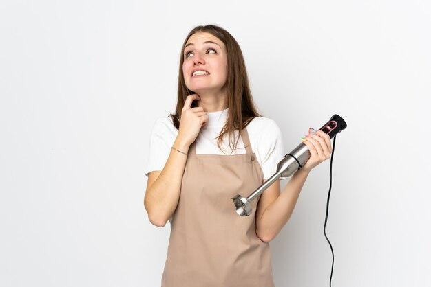 Młoda kobieta używa ręki blender odizolowywającego na białym główkowaniu pomysł