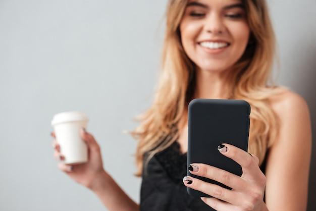 Młoda kobieta używa ruchomego telefon i bierze oddaloną filiżankę