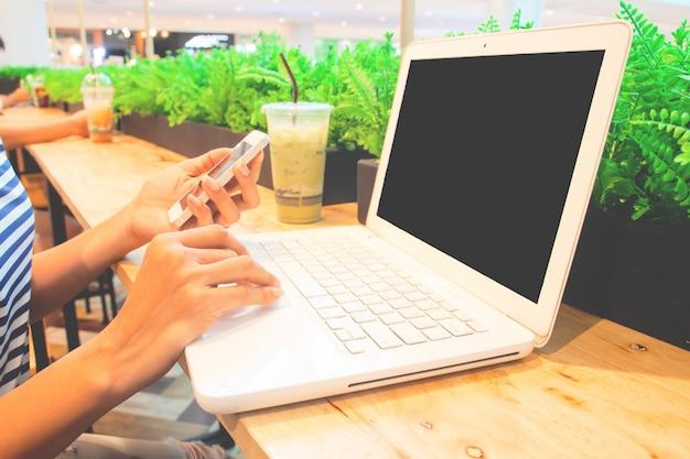 Młoda kobieta używa smartphone i laptop w nowożytnej stylowej kawiarni