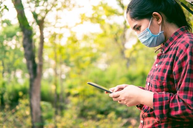 Młoda kobieta używa smartphone, ogólnospołeczny dystansowy pojęcie.