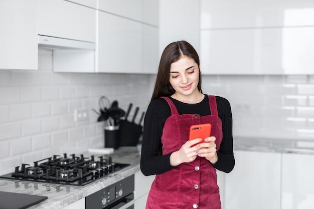 Młoda kobieta używa smartphone opiera przy kuchennym stołem z kawowym kubkiem i organizatorem w nowożytnym domu. uśmiechnięta kobieta czyta telefon wiadomość. brunetki szczęśliwa dziewczyna pisać na maszynie wiadomość tekstową