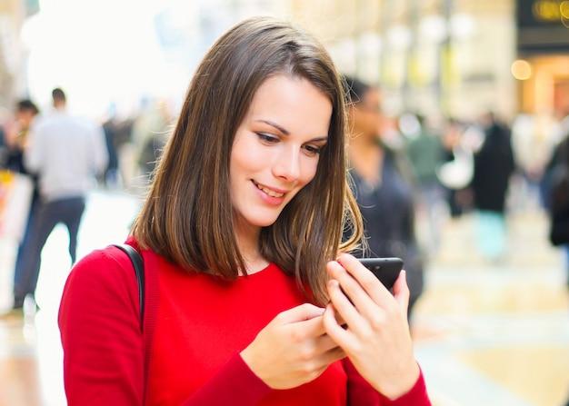 Młoda kobieta używa smartphone plenerowego