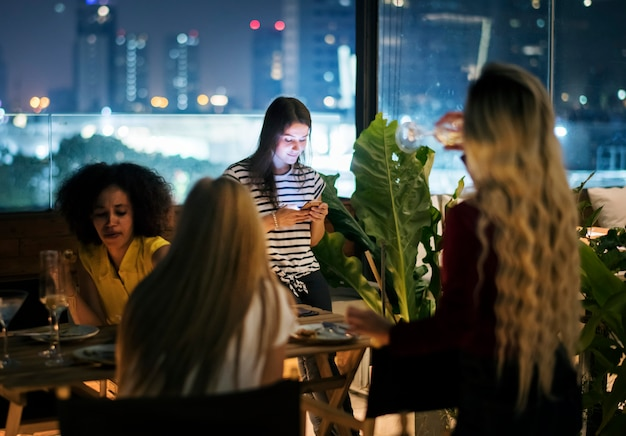 Młoda kobieta używa smartphone przy obiadową nocą ma interakcję z przyjaciółmi
