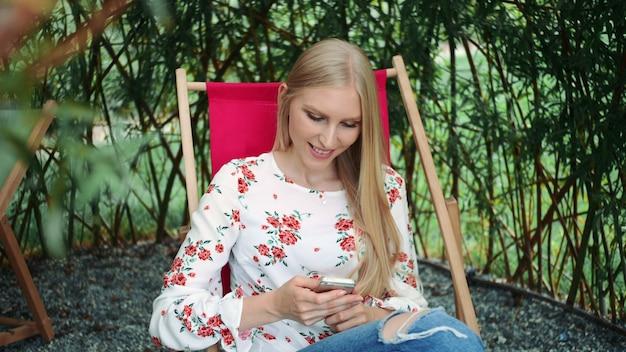 Młoda kobieta używa smartphone w rośliny altanie.
