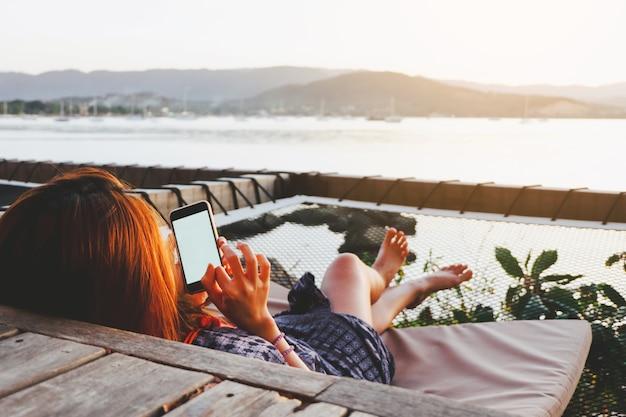 Młoda kobieta używa smartphone z pustym ekranem podczas gdy kłamający bocznego morze z wieczór zmierzchem.