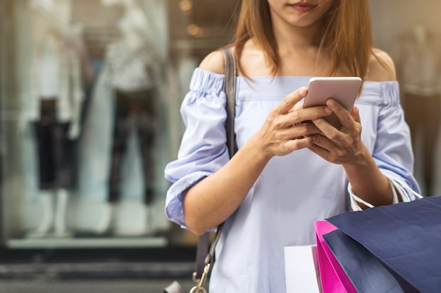 Młoda kobieta używa smartphone z torba na zakupy przy centrum handlowym na czarny piątek,