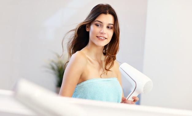Młoda kobieta używa suszarki do włosów w łazience rano