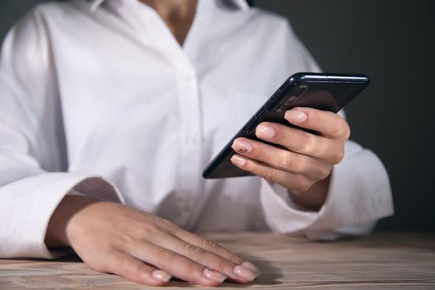 Młoda Kobieta Używa Swojego Smartfona Przy Stole Premium Zdjęcia