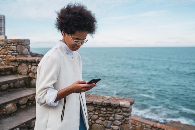 Młoda kobieta używa swojego telefonu komórkowego.