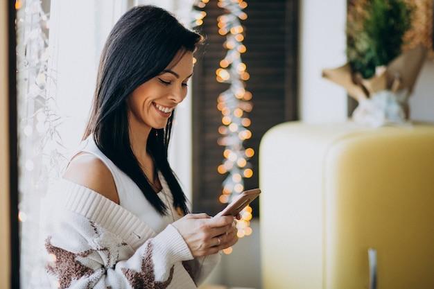 Młoda kobieta używa telefon i pozycję okno