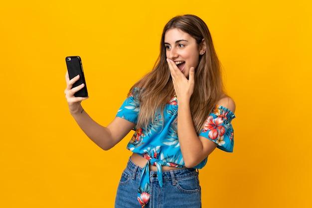 Młoda kobieta używa telefon komórkowego nad odosobnioną kolor żółty ścianą z niespodzianką i szokującym wyrazem twarzy