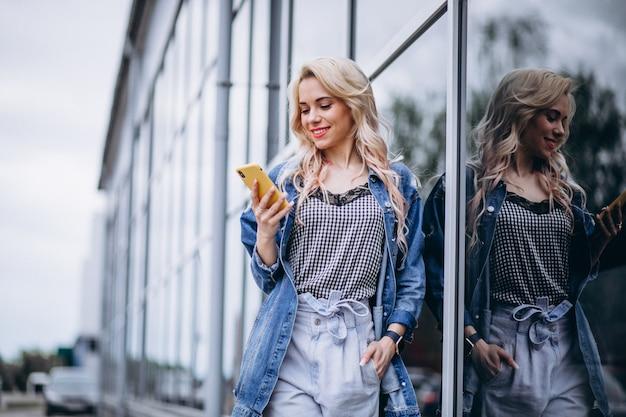Młoda kobieta używa telefon na zewnątrz