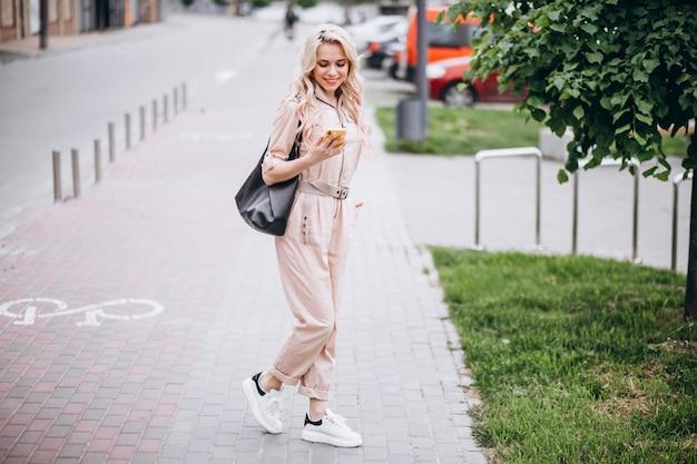 Młoda kobieta używa telefon outside w parku