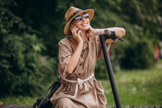 Młoda kobieta używa telefon w parkowym obsiadaniu na ławce hulajnoga