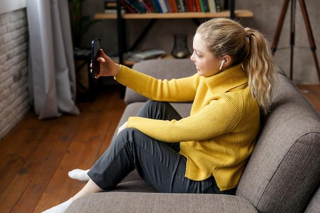 Młoda kobieta używa telefonu do połączenia wideo z przyjaciółmi