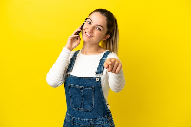 Młoda kobieta używa telefonu komórkowego na odosobnionym żółtym tle, wskazując przód z radosnym wyrazem twarzy