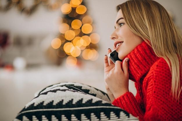 Młoda kobieta używa telefonu na boże narodzenie
