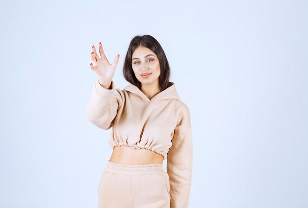Młoda kobieta, używając otwartych rąk do prezentowania i rozmawiania o czymś