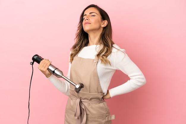 Młoda kobieta używająca blendera ręcznego na izolowanym różowym tle, cierpiąca na ból pleców za wysiłek