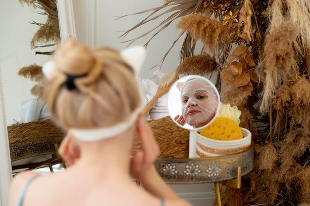 Młoda kobieta używająca maski na twarz do samoopieki