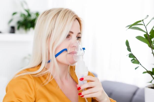 Młoda kobieta używająca nebulizatora na astmę i choroby układu oddechowego w domu