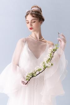 Młoda kobieta w akcji sztuki na białym tle na białej ścianie. styl retro, porównanie koncepcji epok. piękna modelka jak księżniczka, królowa lub księżna, staromodna.