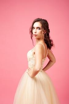 Młoda kobieta w balowej sukni bez rękawów pozuje na odosobnionym tle piękną brunetką z...