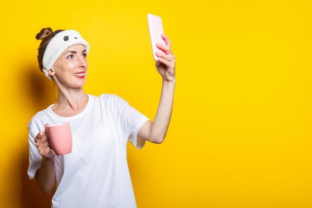 Młoda kobieta w bandażach do snu komunikuje się przez czat wideo i filiżankę kawy na żółtym tle.