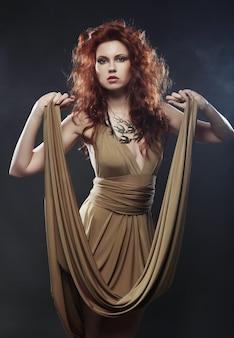 Młoda kobieta w beżowej długiej sukni