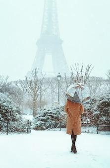Młoda kobieta w beżowym płaszczu idzie pod parasolem w śnieżnym zimowym paryżu
