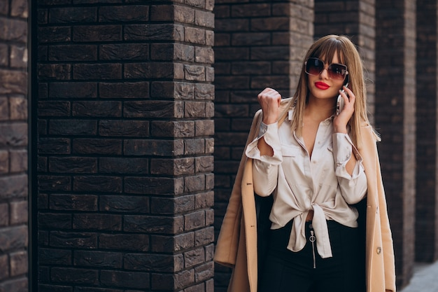Młoda kobieta w beżowym płaszczu, korzystająca z telefonu na ulicy